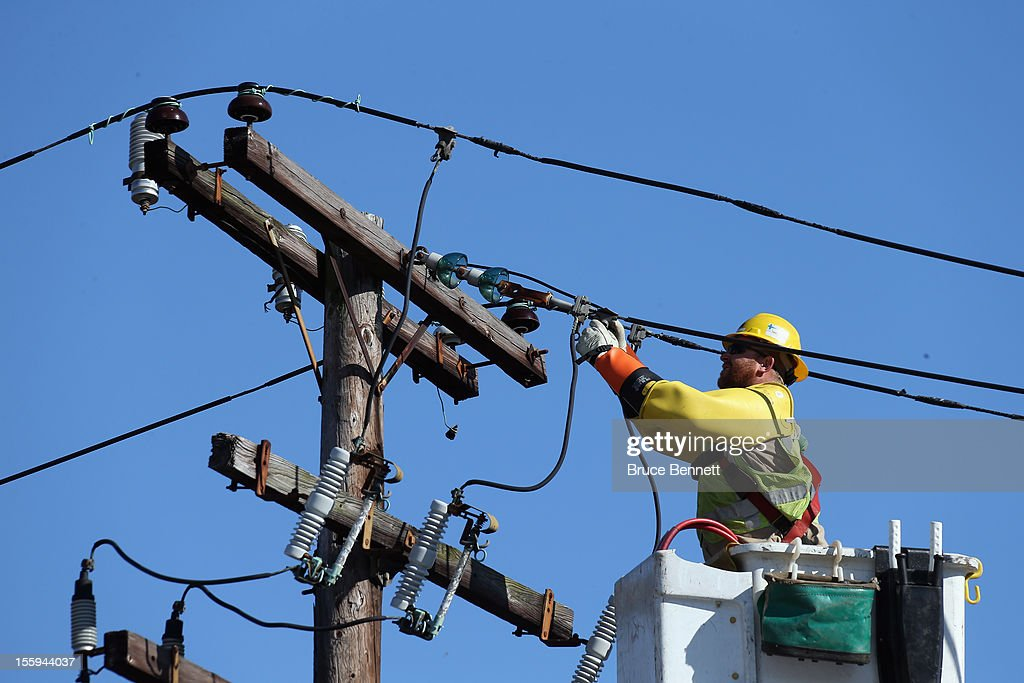 A worker repairs electrical lines as Long Islanders continue their clean up efforts in the aftermath of Superstorm Sandy on November 9, 2012 in Plainview, New York. New York Gov. Andrew M. Cuomo has said that the economic loss and damage to homes and businesses caused by Sandy could total $33 billion in New York, according to published reports.