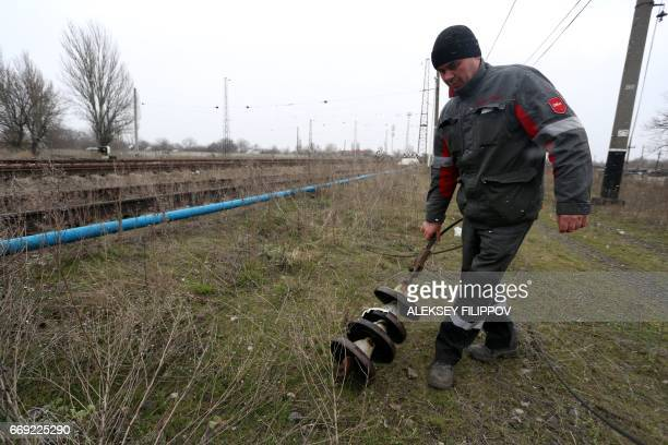 A worker repairs power lines damaged by shelling between Ukrainian forces and the Russianbacked rebels near the governmentheld town Avdiivka Donetsk...
