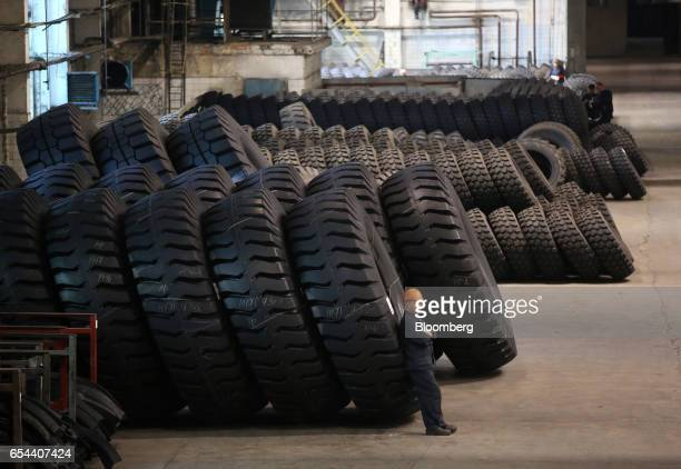 A worker rests against a group of large 4000R57 sized tires in the control room at the Belshina JSC tire factory in Babruysk Belarus on Thursday...