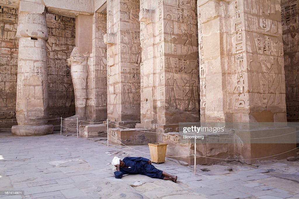 A worker rests on the ground in the ruins of the ancient Temple of Rameses III in Luxor, Egypt, on Wednesday, April 24, 2013. Egypt ranked last in terms of security and safety on the World Economic Forum's 2013 Travel and Tourism Competitiveness Index. Photographer: Shawn Baldwin/Bloomberg via Getty Images
