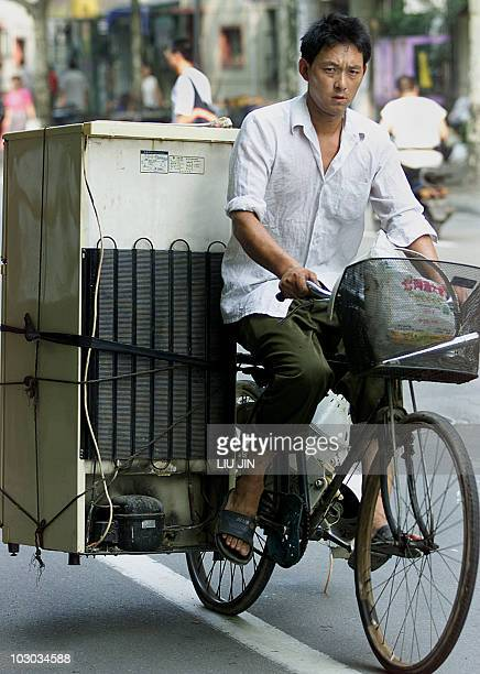 A worker rides a bicycle carrying an old fridge in Shanghai 19 August 2002 China's booming port city of Shanghai saw its economy steam ahead in the...
