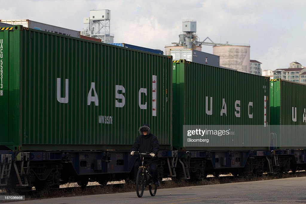 A worker rides a bicycle past a train loaded with containers at the Uiwang Inland Container Depot (ICD) in Uiwang, South Korea, on Monday, Nov. 26, 2012. South Korea's current-account surplus narrowed to a two-month low after imports of machinery and equipment increased. Photographer: SeongJoon Cho/Bloomberg via Getty Images