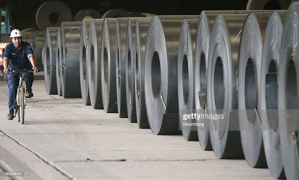 A worker rides a bicycle past coils of hot-rolled steel outside the hot strip mill area of the PT Krakatau Steel plant in Cilegon, Banten province, Indonesia, on Thursday, Feb. 21, 2013. Krakatau Steel is Indonesia's biggest maker of the metal. Photographer: Dadang Tri/Bloomberg via Getty Images