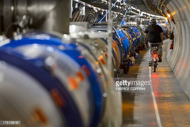 A worker rides his bicycle in a tunnel of the European Organisation for Nuclear Research Large Hadron Collider during maintenance works on July 19...