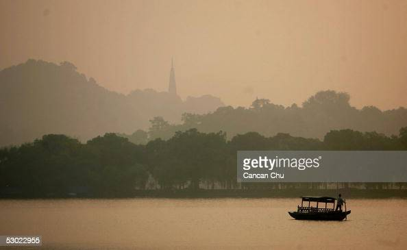 A worker rides in a boat during sunrise at the West Lake on June 3 2005 in Hangzhou Zhejiang Province of China The West Lake is one of China's most...