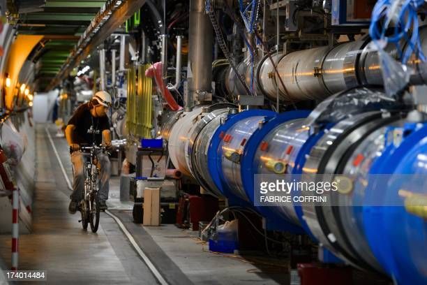 A worker rides on his bicycle in the CERN's Large Hadron Collider tunnel during maintenance works on July 19 2013 in Meyrin near Geneva Tests at the...