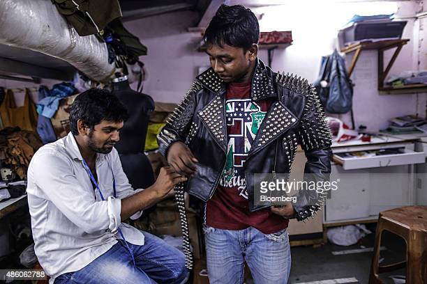 A worker right wears a leather jacket for a photograph at a leather workshop in the Dharavi slum area of Mumbai India on Saturday Aug 29 2015 India's...