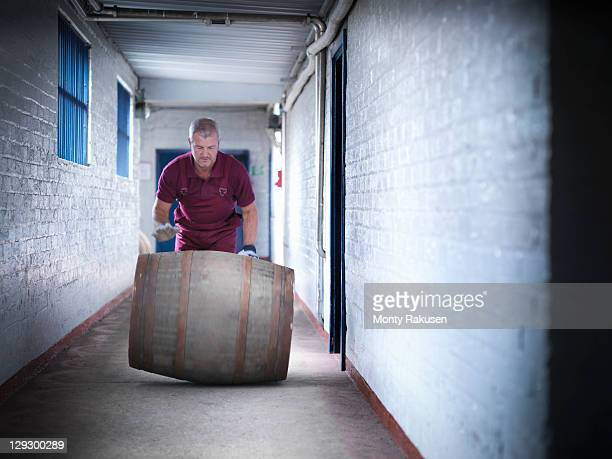 Worker rolling whisky barrel in distillery