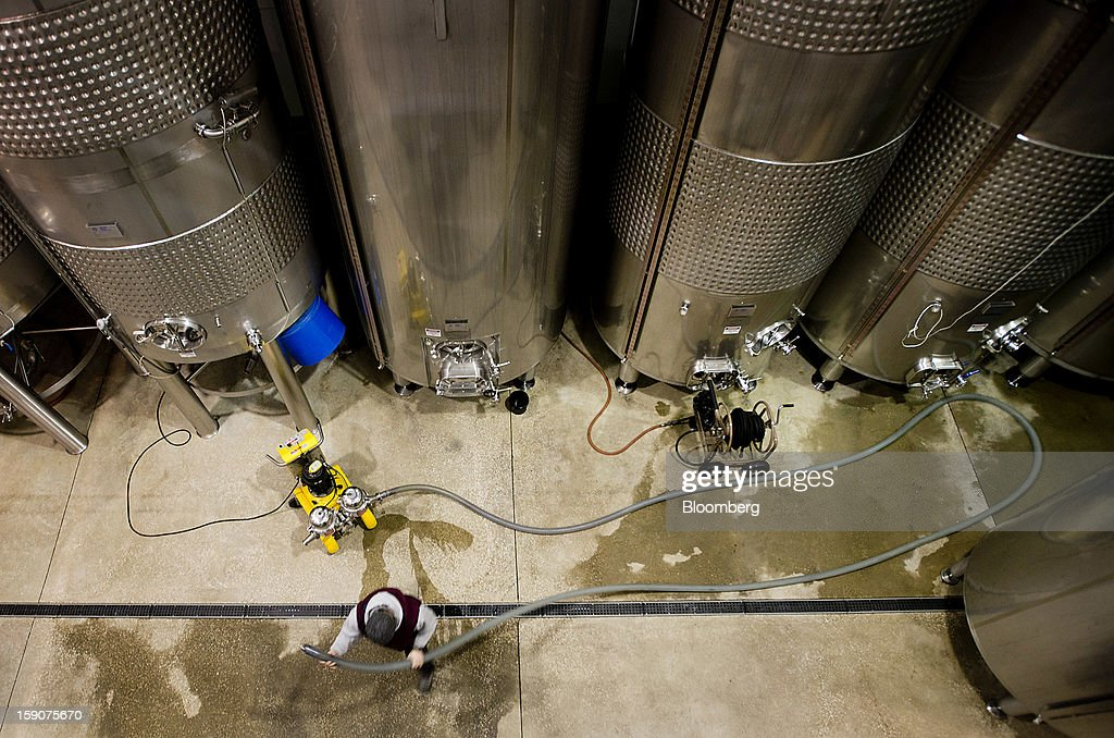 A worker runs hoses from a filtration system while filtering red wine from a fermenting tank at the Ferrante Winery in Geneva, Ohio, U.S., on Friday, Jan. 4, 2013. Ice wine is a type of dessert wine produced from grapes that have been frozen while still on the vine, because the sugars and other dissolved solids do not freeze, but the water does, this allows a more concentrated grape must to be pressed. Photographer: Ty Wright/Bloomberg via Getty Images