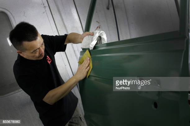 Worker sanding to new painted rear door at mohenic garages in Paju South Korea A 20yearold beat up Hyundai SUV isn't anyone's idea of a dream car But...