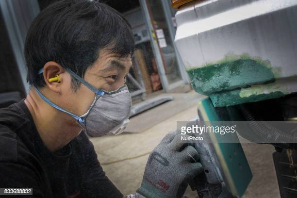 Worker sanding to rear bumper at mohenic garages yard in Paju South Korea A 20yearold beat up Hyundai SUV isn't anyone's idea of a dream car But used...
