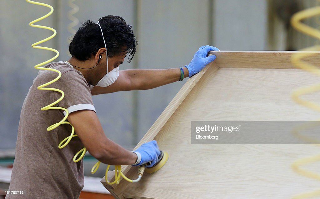 A Worker Sands A Custom Piece Of Furniture At The At Baker Road Furniture  Manufacturing Facility