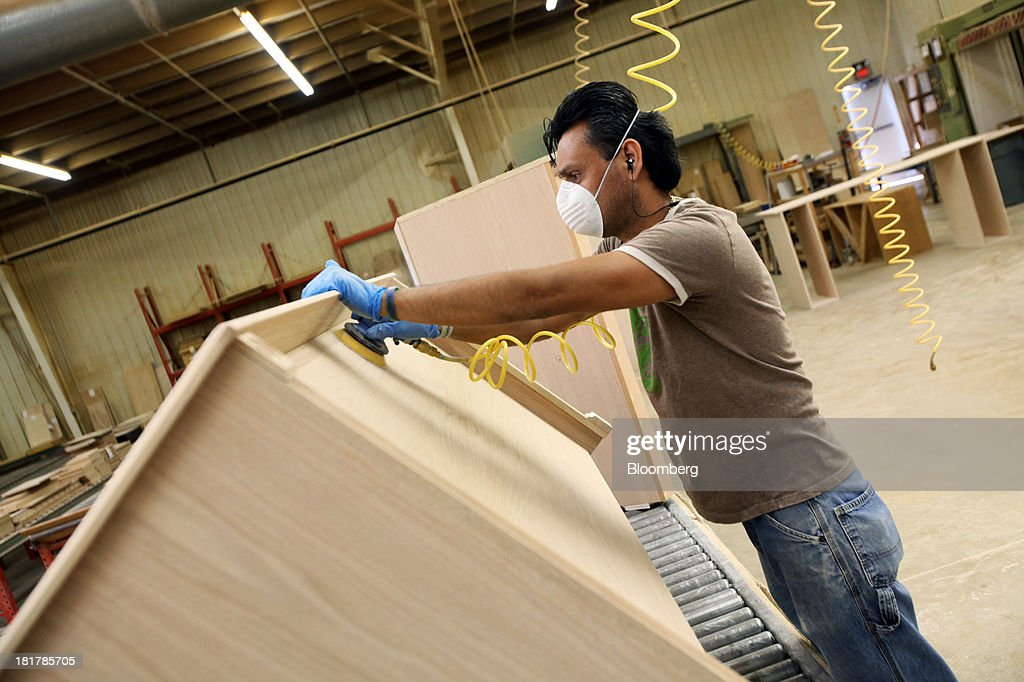 A Worker Sands A Piece Of Custom Furniture At The At Baker Road Furniture  Manufacturing Facility