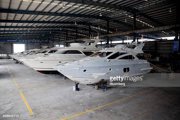 A worker sands the hull of a Sunbird Yacht Co Ltd Phoenix 58foot yacht at the company's manufacturing facility inside the Zhuhai Gaolan Port Economic...
