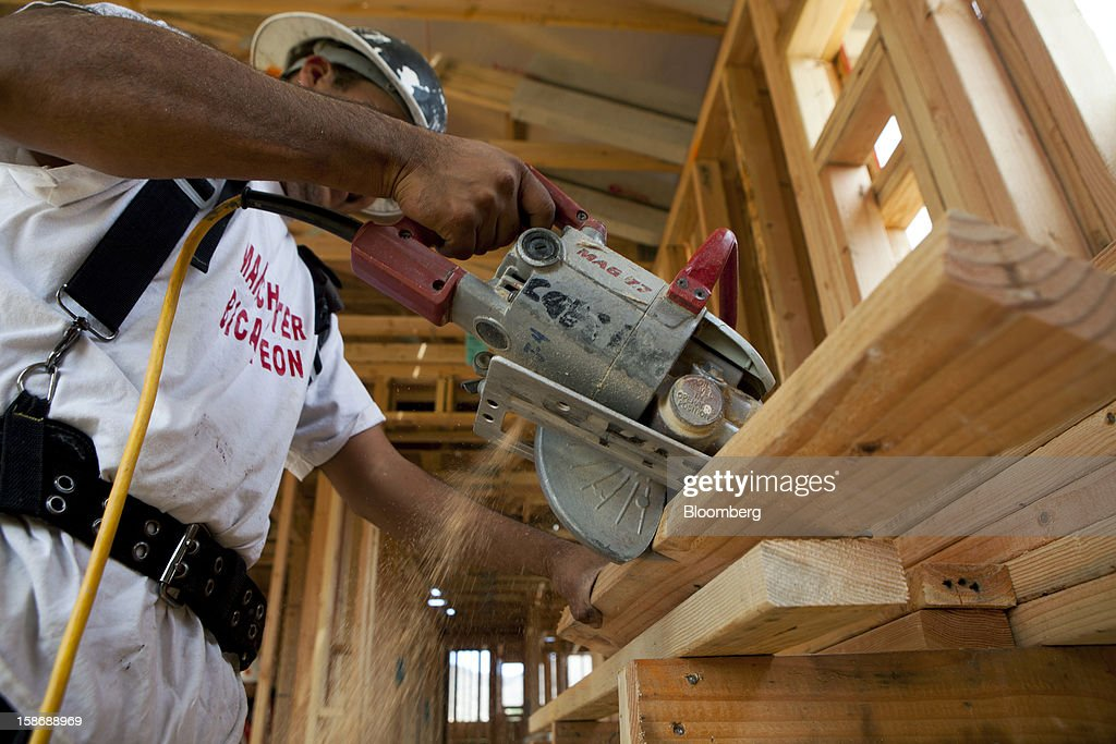 A worker saws lumber inside a house under construction at Davidson Communities LLC's Arista at The Crosby development in Rancho Santa Fe, California, U.S., on Friday, Dec. 21, 2012. New home sales climbed to a 380,000 annual rate in November, the most since April 2010, according to the median forecast of 60 economists surveyed by Bloomberg before Dec. 27 figures from the Commerce Department. Photographer: Sam Hodgson/Bloomberg via Getty Images