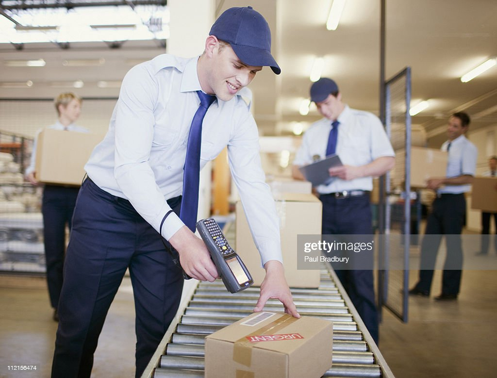 Worker scanning box on conveyor belt in shipping area : Stock Photo