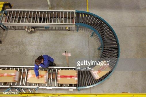 Worker scanning boxes on a conveyor belt