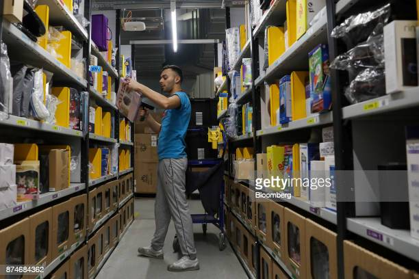 A worker scans an item for a customer's order at an Amazoncom Inc fulfillment center in Peterborough UK on Wednesday Nov 15 2017 As Amazon's share of...