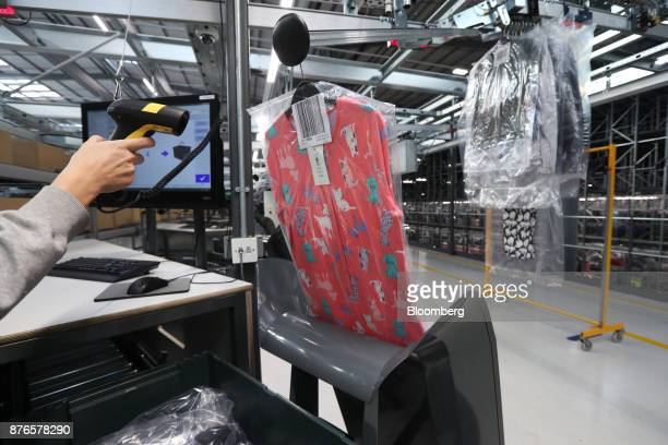 A worker scans and packs hanging garments at the John Lewis Plc customer fulfilment and distribution centre in Milton Keynes UK on Friday Nov 17 2017...