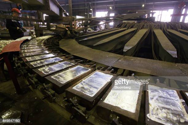 A worker scrapes the surface from cooling zinc ingot in the rotary foundry room at the Chelyabinsk Zinc Plant operated by Ural Mining and...