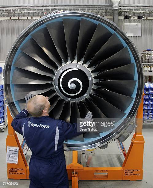 A worker scrubs the turbine of an aircraft jet engine August 23 2006 at the RollsRoyce aircraft engine factory in Berlin Germany The factory a...