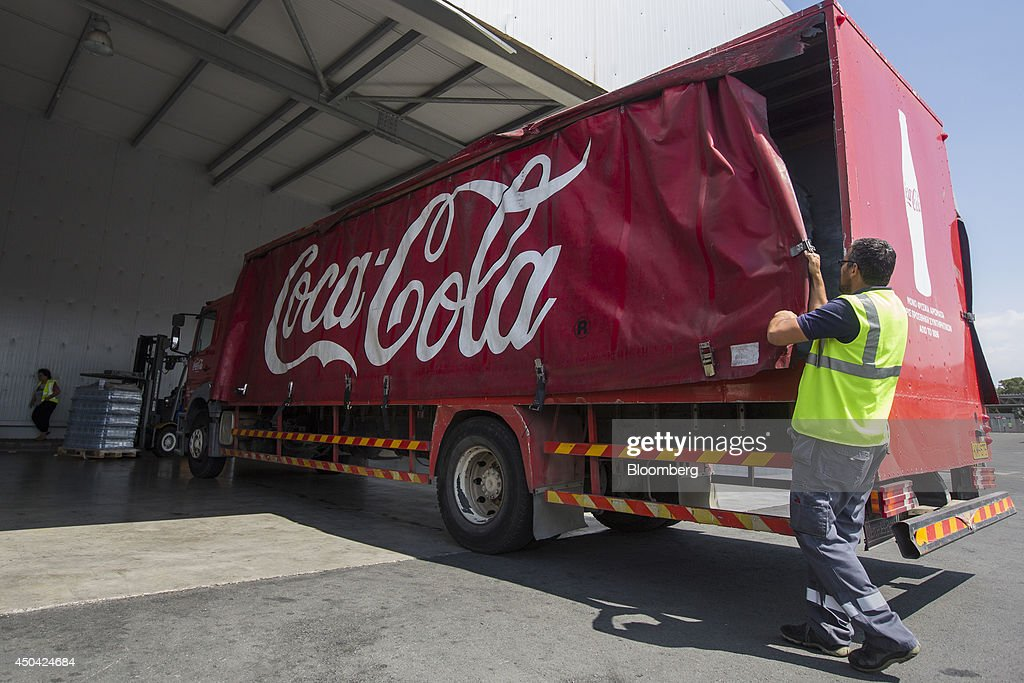 A worker seals a Coca-Cola branded distribution truck ahead of a delivery of beverages at the Lantis Bros Ltd. bottling plant, part of the Coca-Cola Hellenic Group, in Nicosia, Cyprus, on Tuesday, June 10, 2014. Zug, Switzerland-based Coca-Cola Hellenic Bottling Co., which distributes Coca-Cola products in countries including Russia, wants to move away from using imported sugar for its Russian operations by 2015. Photographer: Andrew Caballero-Reynolds/Bloomberg via Getty Images
