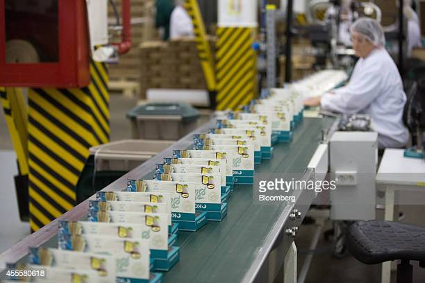 A worker seals candy boxes from the Comilfo confectionary range as they move along a conveyor belt at the Rossiya chocolate factory operated by...