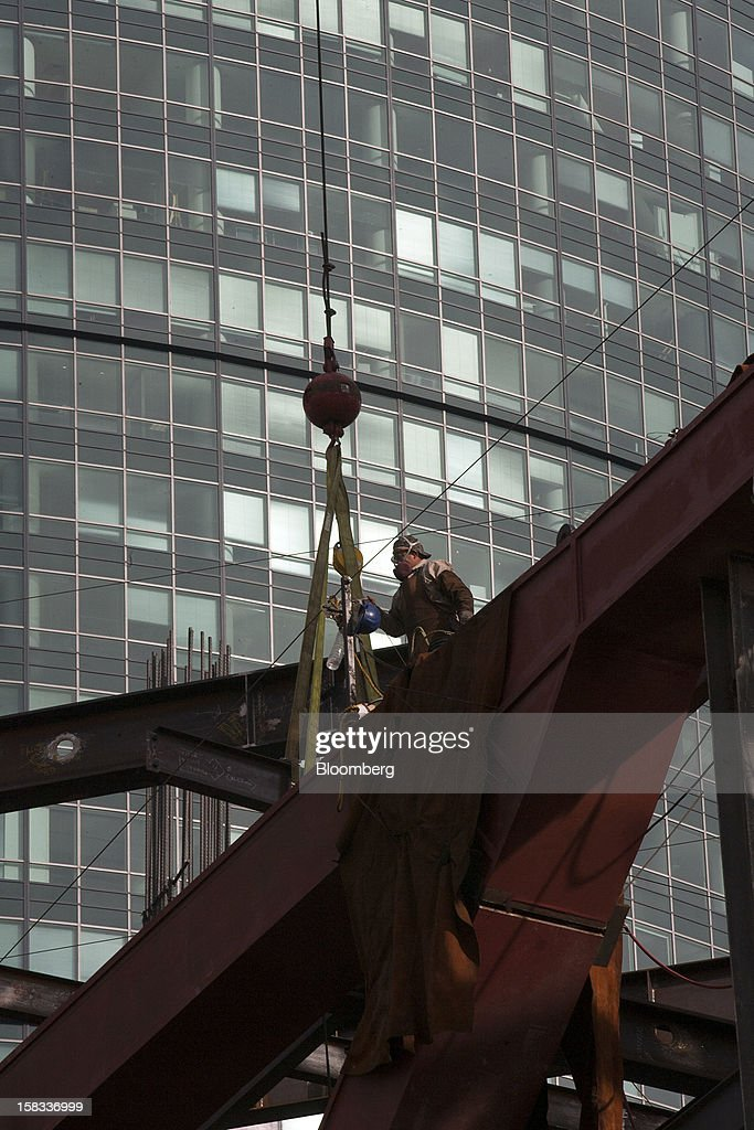 A worker secures a load of building materials at the construction site of the BBVA Bancomer Tower in Mexico City, Mexico, on Thursday, Dec. 13, 2012. The office for BBVA Bancomer, the Mexican unit of Banco Bilbao Vizcaya Argentaria SA, Spain's second-biggest bank, will have 50 floors and accommodate about 4,500 employees when it is completed. Mexico City's famous Torre Mayor building stands in the background. Photographer: Susana Gonzalez/Bloomberg via Getty Images