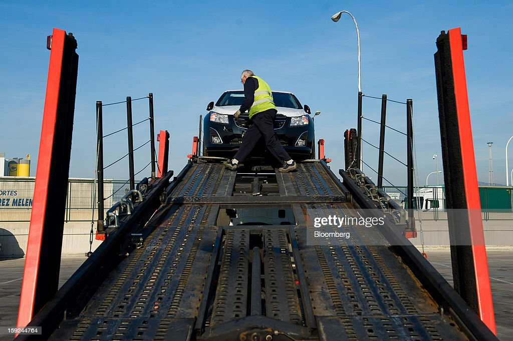 A worker secures a new imported General Motors Co. Chevrolet automobile onto a transporter truck for shipping at Barcelona port in Barcelona, Spain, on Thursday, Jan. 10, 2013. Spanish exports grew the least in five months in September as the euro area relapsed into a recession and the region's fourth-largest economy continued to contract. Photographer: David Ramos/Bloomberg via Getty Images