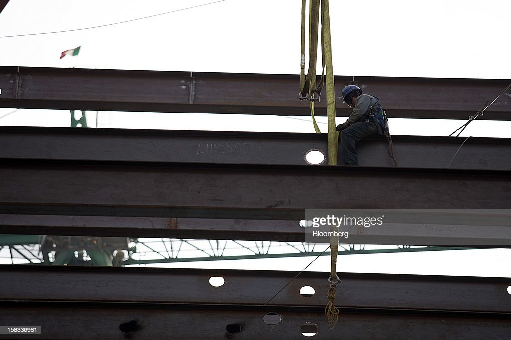 A worker secures an iron beam at the construction site of the BBVA Bancomer Tower in Mexico City, Mexico, on Thursday, Dec. 13, 2012. The office for BBVA Bancomer, the Mexican unit of Banco Bilbao Vizcaya Argentaria SA, Spain's second-biggest bank, will have 50 floors and accommodate about 4,500 employees when it is completed. Photographer: Susana Gonzalez/Bloomberg via Getty Images