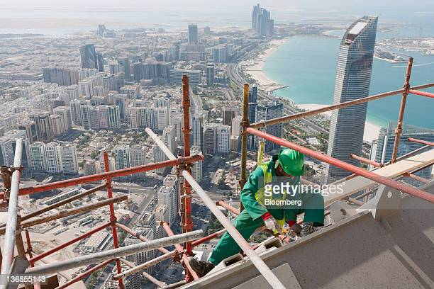 A worker secures scaffolding on a residential tower construction above the Central Market an Aldar PJSC project in Abu Dhabi United Arab Emirates on...