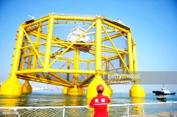 A worker sees off the smart deepsea salmon farm leaving the shipyard in east China's Shandong province for a journey to Norway on June 14 2017 in...