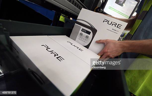 A worker selects a boxed Pure Evoke D4 digital radio from a crate as he processes a customer's order at the John Lewis Plc semiautomated distribution...