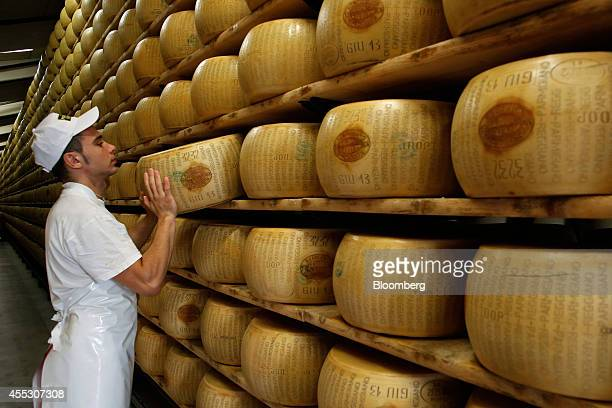 A worker selects a whole ParmigianoReggiano cheese from a storage rack ahead of inspection at Coduro cheesemakers in Fidenza Italy on Thursday Sept...