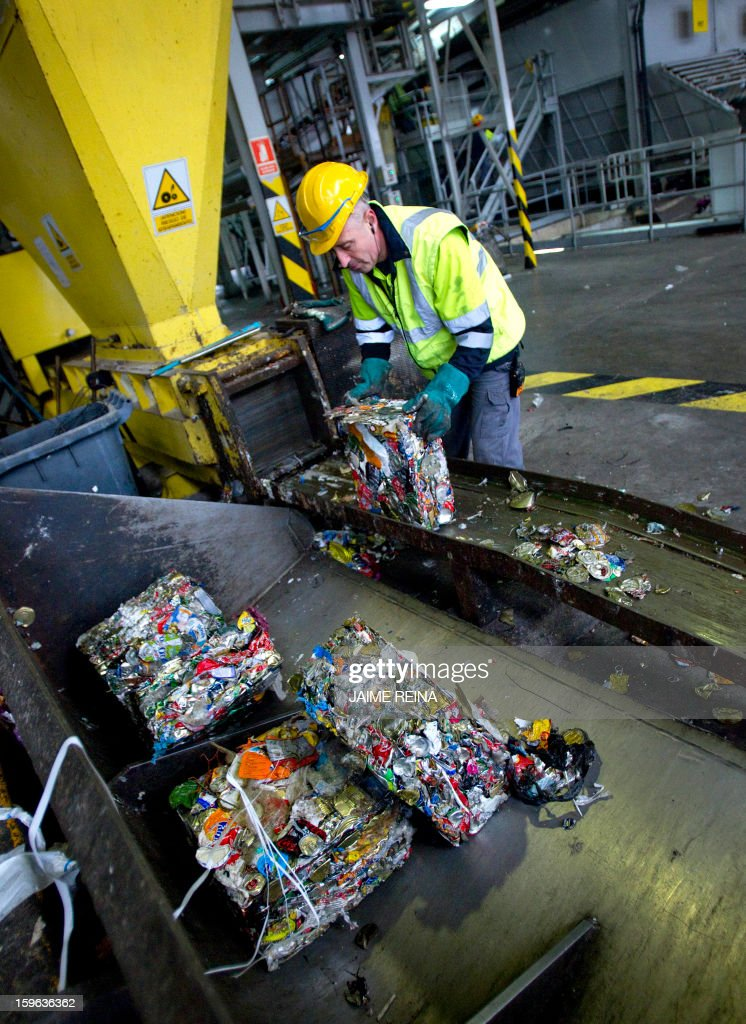 A worker separates garbage for recycling at a waste treatment plant in Palma de Mallorca on January 17, 2013. AFP PHOTO / Jaime REINA