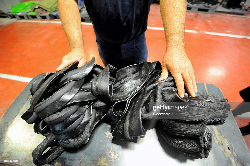 A worker separates tubes of industrial rubber produced by a pressure machine at the Tigar AD rubber factory in Pirot, Serbia, on Tuesday, Dec. 11, 2012. The Serbia-based company in 2008 acquired the Century Division of Hunter Boot Ltd. and specializes in safety boots. Photographer: Oliver Bunic/Bloomberg via Getty Images