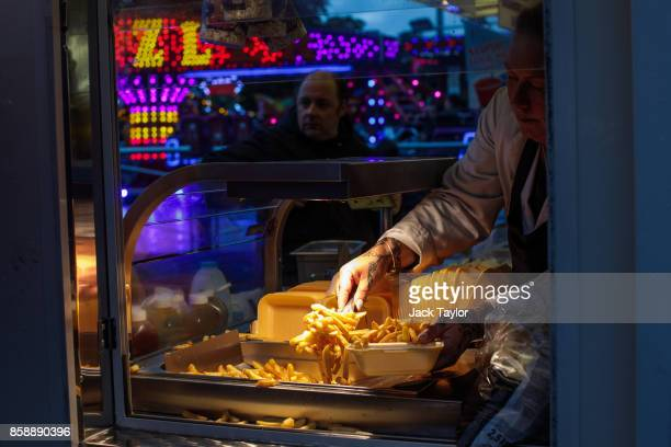 A worker serves chips at the Nottingham Goose Fair in the Forest Recreation Ground on October 7 2017 in Nottingham England The annual goose fair...
