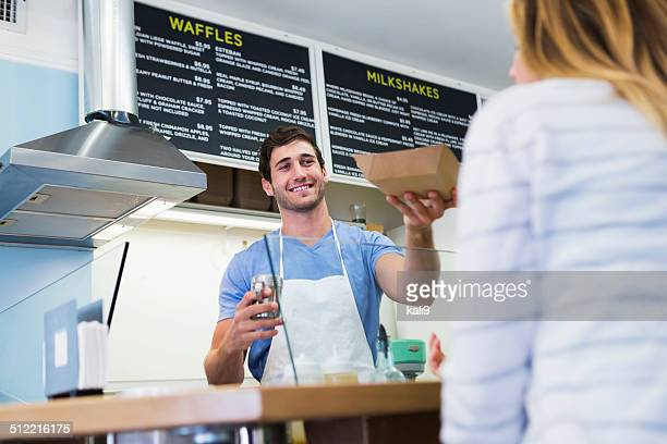 Worker serving customer in waffle shop
