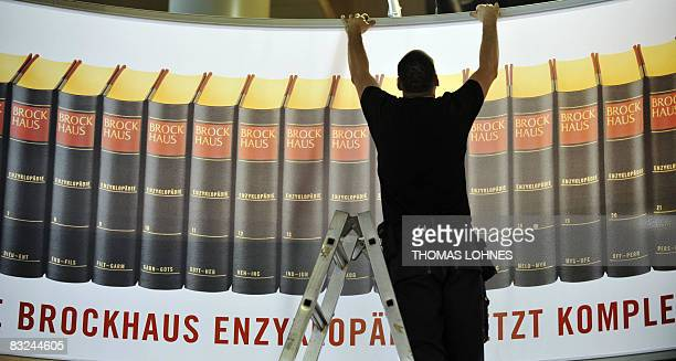 A worker sets up a poster at the stand of the Brockhaus encyclopedia at the fair grounds of the 60th Frankfurt Book Fair on October 13 2008 in...