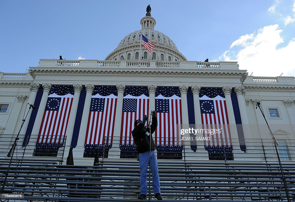 A worker sets up microphones at the US Capitol as preparations continue for the second inauguration of US President Barack Obama in Washington on January 18, 2013. Crowds may be smaller at the January 21 inauguration than when Barack Obama was first sworn into office in 2009, but security is as tight as ever, with experts warning a 'lone wolf' would pose the greatest threat. Between 500,000 and 800,000 people are expected to pass through the National Mall, the immense greenway that leads up to the Capitol, compared to the 1.8 million spectators who came to applaud Obama four years ago. AFP PHOTO/Jewel Samad