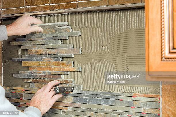 Worker Setting a New Kitchen Backsplash Stone