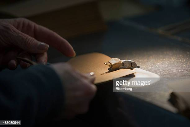 A worker sews a piece of leather while making boots at the LL Bean Inc manufacturing facility in Brunswick Maine US on Friday Feb 6 2015 Over 450...