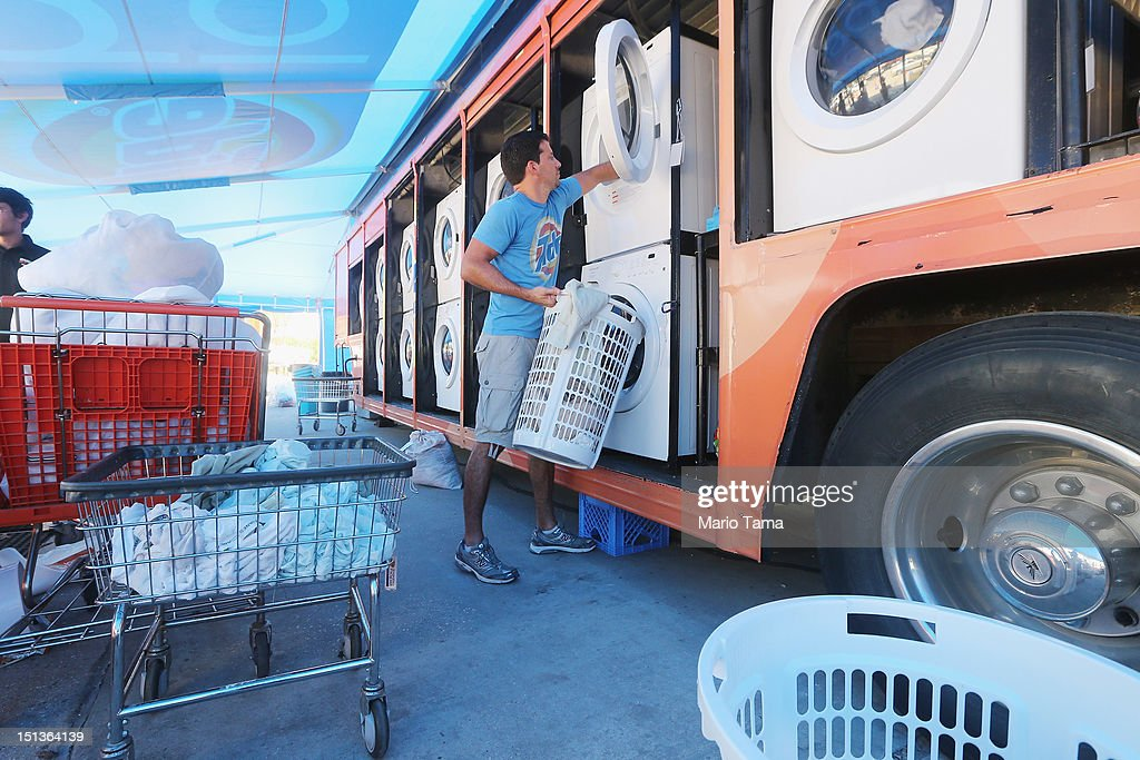 Worker Shane Grady collects a resident's laundry being washed for free at the Tide Loads of Hope mobile laundromat set up for those affected by...