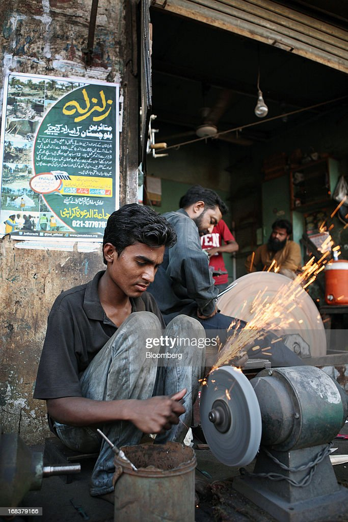 A worker sharpens an iron knife on a grinder in Karachi, Pakistan, on Wednesday, May 8, 2013. Pakistan is to hold parliamentary elections on May 11. According to opinion polls, Nawaz Sharif of the Pakistan Muslim League-N (PMLN) leads Imran Khan of Pakistan Tehrik-e-Insaf (PTI) in the race to replace president Asif Ali Zadari and become Pakistan's 12th president. Photographer: Asim Hafeez/Bloomberg via Getty Images