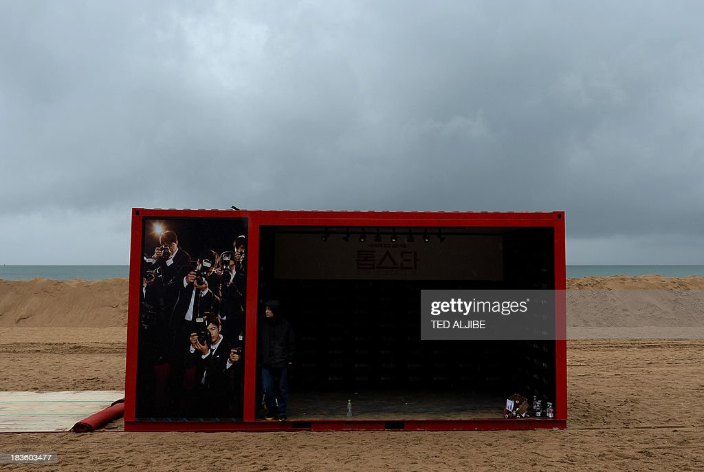 A worker shelters from rain inside a container van as they remove decorations at the Busan International Film Festival (BIFF) village along Haeundae beach in Busan on October 8, 2013, ahead of preparations for Typhoon Danas expected to pass through the coastal city early on October 9. Packing winds of up to 180 kilometres (112 miles) per hour near its centre, Danas was churning northwest towards the southern Okinawa island chain October 7, and was expected to reach a point off the western coast of Kyushu island by early October 9.