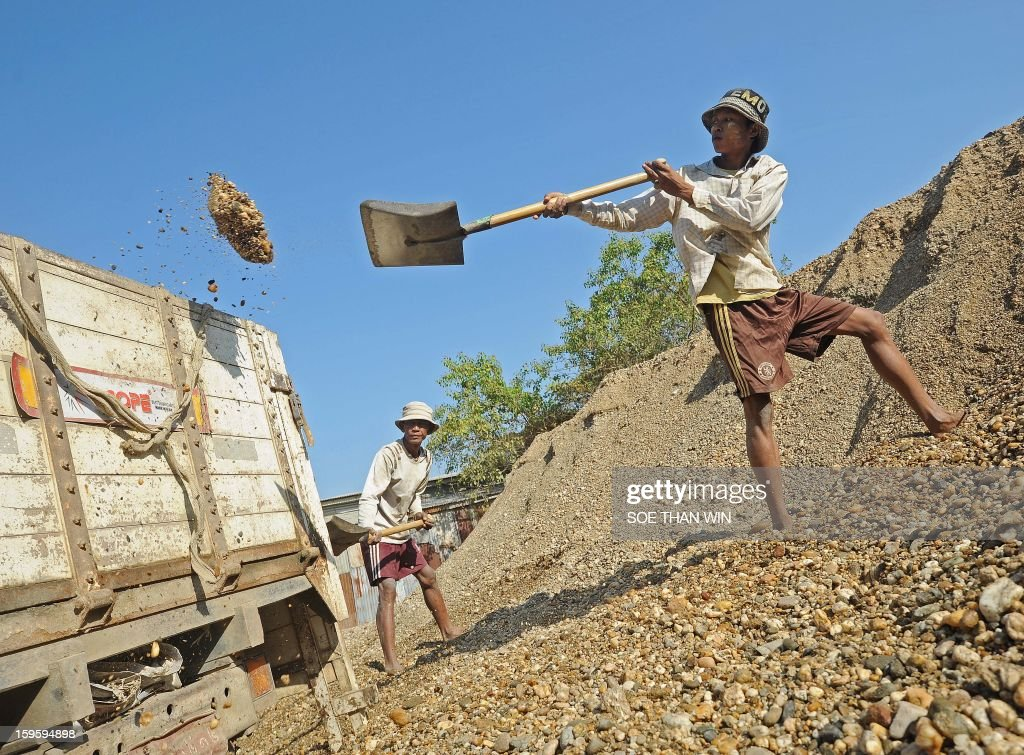 A worker shifts pebbles at a pebble cleaning yard, used in concrete mix, in Yangon on January 17, 2013. Myanmar is one of the poorest countries in Asia after decades of economic mismanagement and isolation under army rule, but could become Asia's next economic engine if it enacts vast reforms, the IMF said in November of 2012. AFP PHOTO/ Soe Than WIN