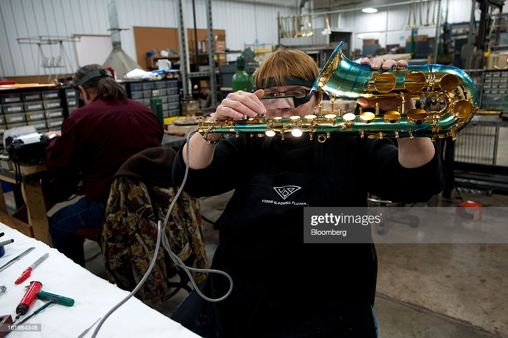 A worker shines a light through the tuning holes of a saxophone during assembly in the manufacturing department of the E.K Blessing Co. in Elkhart, Indiana, U.S., on Thursday, Feb. 7, 2013. Photographer: Ty Wright/Bloomberg via Getty Images