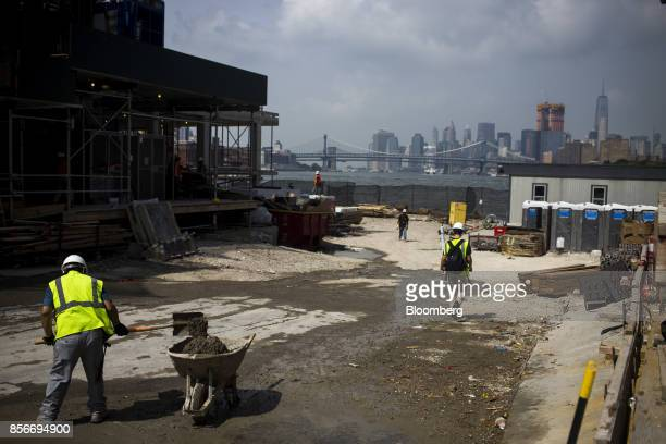 A worker shovels dirt into a wheel barrow during construction at 420 Kent Avenue and 416 Kent Avenue apartment developments in the Williamsburg...