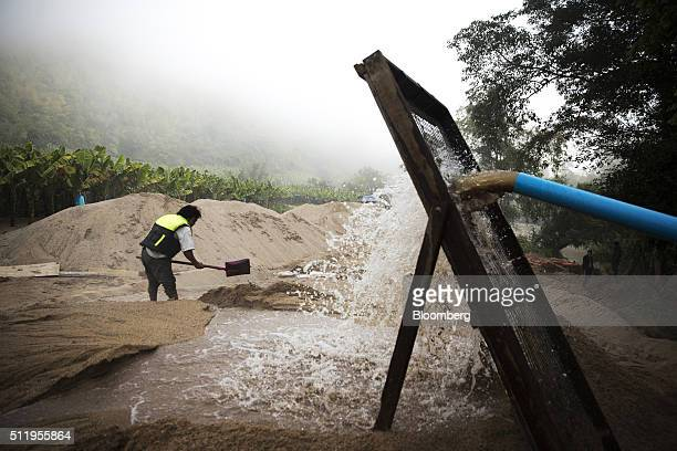 A worker shovels sand at the end of a makeshift slurry pipeline on the banks of a river at a sand dredging site near Kengtung Shan State Myanmar on...