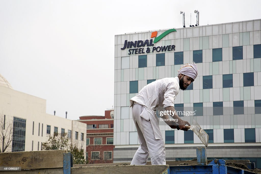 A worker shovels sand in the back of a truck in front of Jindal Steel & Power Ltd. signage displayed atop a commercial building in Gurgaon, India, on Wednesday, March 26, 2014. Indian stocks rose, sending the benchmark index to a record, after the rupee rose to an eight-month high and sovereign bonds gained on speculation the worlds largest democracy will elect a government capable of reviving economic growth. Photographer: Kuni Takahashi/Bloomberg via Getty Images